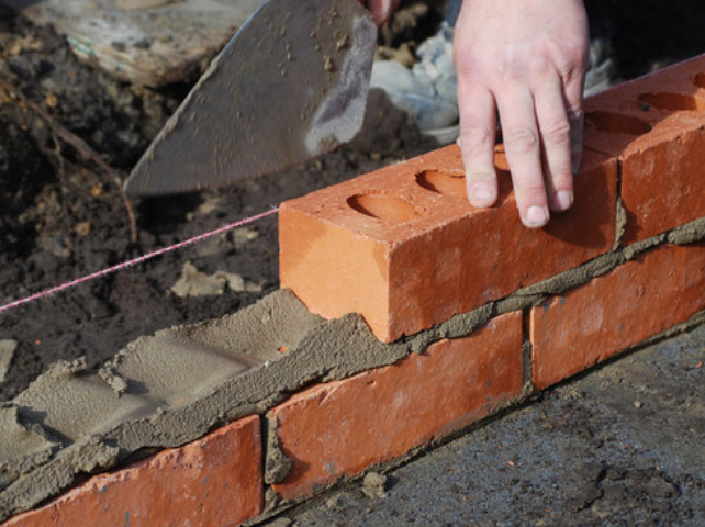 Bricklayer laying a course of bricks